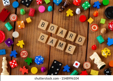 """Board Game"" spelled out in wooden letter tiles. Surrounded by dice, cards, and other game pieces on a wooden background"