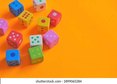 Board games concept. games of chance.  Multicolored cubes set close-up on a bright orange background.Figures and numbers concept. copy space.