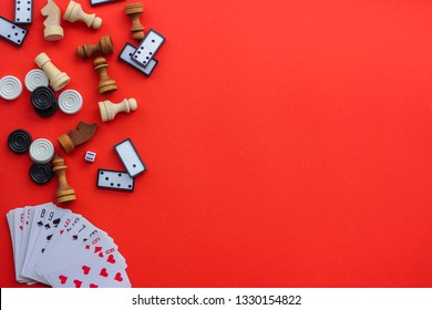 Board games on a red background: playing cards, dominoes, checkers and chess. the view from the top, place under the text