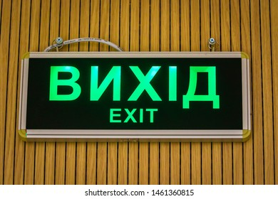 A board with a green (EXIT) in Ukrainian and English hangs on the wall