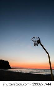 a board less basketball rim on the beach