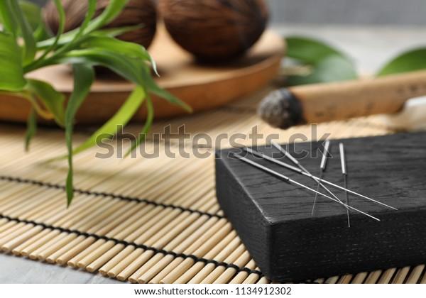 Brett mit Akupunktur-Nadeln auf Bambusmatte