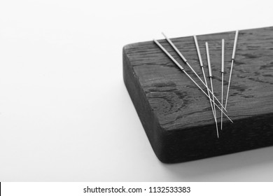 Board with needles for acupuncture on white background