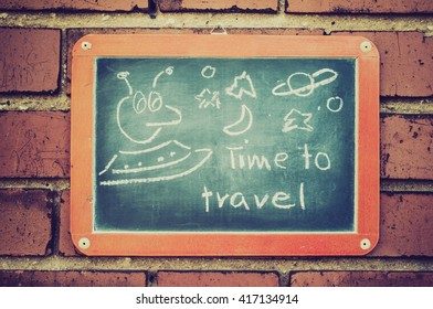 Board on a brick wall with text Time to travel.