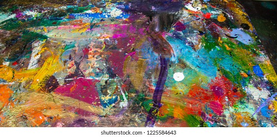 A board (portion of a table top) artists use to mix colors and remove excess paint from their brushes in an art studio, not a piece of art, rather a receptical for excess paint a huge painters pallet