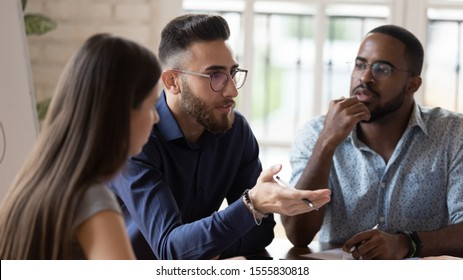 In board room gathered multi racial business people focus on serious middle eastern ethnicity team leader talking about strategy, corporate goals, share ideas, solve problems together at group meeting