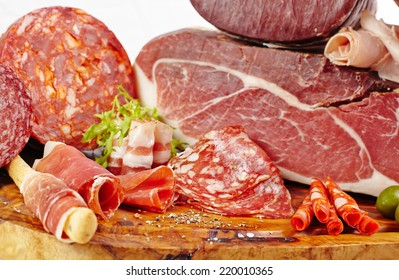 Board with salami and ham on wooden board