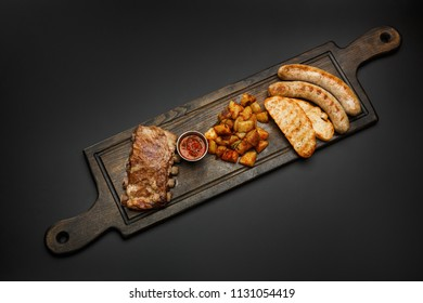 Board with sausages; Ribs, potatoes and sauce for beer isolated on a black background.