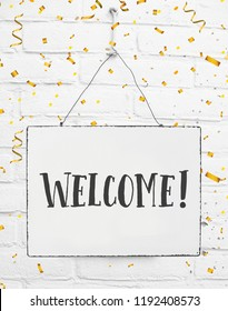 Board sign with text hello welcome come in golden party confetti