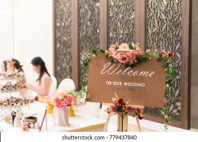 Board sign Welcome to our wedding on wooden background with blossom flower in reception in banquet room for couple new wedding. Beginning of family concept.