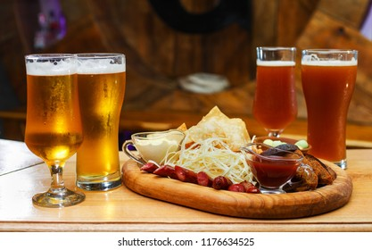 A board with snacks for beer. Board with chips, sausages, rye bread, cheese and red and white sauce. Nearby two glasses of light and dark beer.