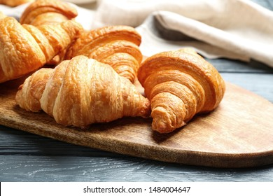 Board with tasty croissants on dark wooden table, closeup. French pastry