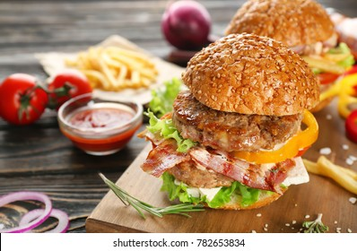 Board with tasty double burgers on table