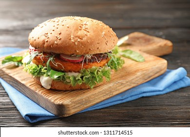 Board with tasty vegetarian burger on wooden table