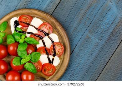 A board with tomato, mozzarella, basil and balsamic vinegar