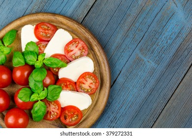 A board with tomato, mozzarella and basil on blue wood