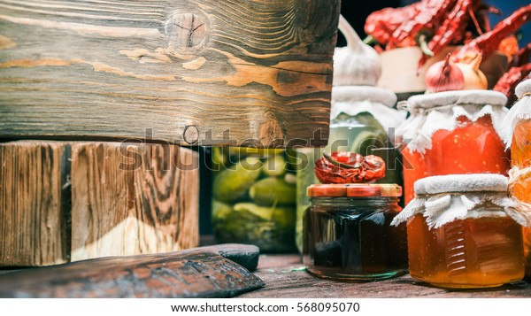 Board of wood hanging in front of vegetable cans assortment. Close up view. Concept of sign in organic food store
