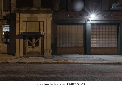 Boarded up entrance to an abandoned factory with classic architectural entrance at night in urban industrial area