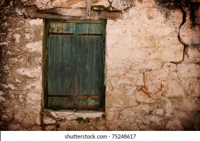 Boarded up green door and window of old cottage in Karia Lefkas Greece