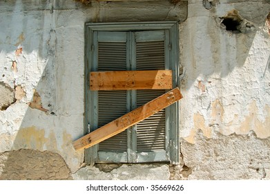 Boarded up old window with blue shutter and peeling paint weathered wall. Abandoned house detail.