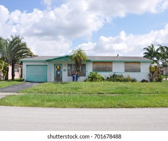Boarded up Suburban Ranch home blue sky clouds USA
