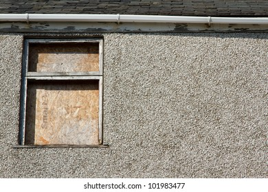 A boarded up window frame in bad repair with missing glass poor guttering a pebble dash wall and slate roof.
