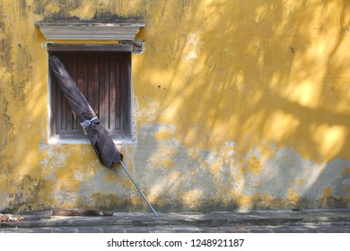Boarded up window, parasol and ancient plastered yellow walls, old quarter Hoi An, Vietnam