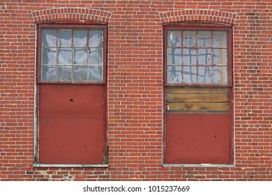 boarded windows in an old brick industrial building