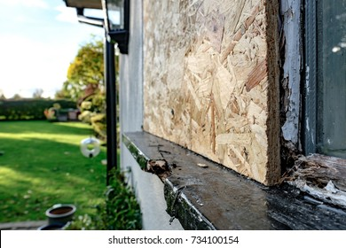 Boarded-up cottage window, seen after a burglary to the property, as the window frame was partially removed to gain access within the property. Damage to the window ledge is also visible.