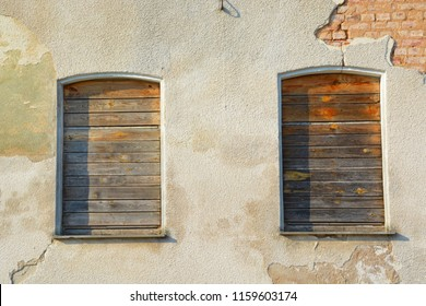 boarded-up windows of an old and broken building - economic downturn ensures boarded-up houses and vacant buildings