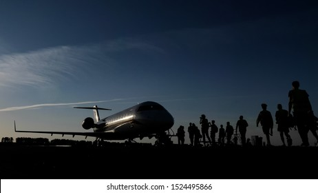 Boarding on flight on runway in airport. Silhouette of passengers approach the aircraft preparing for landing in evening. Passenger jet on airstrip with people near it. Spotting concept.