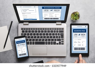 Boarding pass concept on laptop, tablet and smartphone screen over gray table. Flat lay