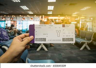 Boarding pass on hand with blur airport terminal background in traveler concept.