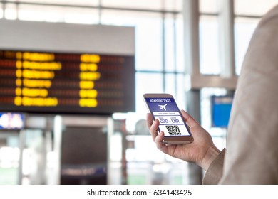 Boarding pass in smartphone. Woman holding phone in airport with mobile ticket on screen. Modern travelling technology and easy access to aeroplane. Terminal and timetable in the blurred background.