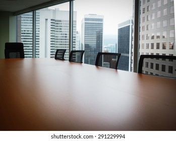 Boardroom table with five chairs, no people, showing view out of upper floor windows of other tall buildings. Modern boardroom with mesh-back chairs, modern brown table with sheen, in business office