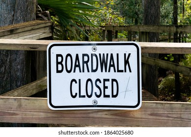 Boardwalk Closed White Sign On A Wood Gate Closing Off A Boardwalk at Lake Mills Park In Florida