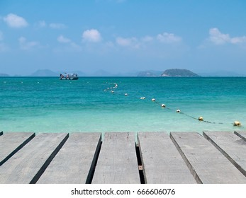 Boardwalk with emerald sea and boat