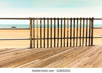 Boardwalk, empty beach and ocean.  Wooden picket railing.  Retro, vintage color palette.