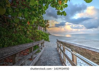 Boardwalk entering North Gulf Shore Beach in Naples Florida at Sunrise in Summer.