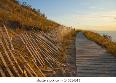 Boardwalk and fence on sandy cliff overlook at sunset