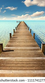 boardwalk to the horizon, turquoise water and blue sky with clouds, paradise landscape