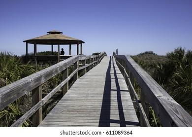 Boardwalk leading to the Atlantic Ocean on Tybee Island near Savannah Georgia and the Tybee Lighthouse.