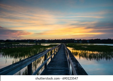 boardwalk leading into a salt marsh with a beautiful sunset and reflection in the water on the South Carolina coast