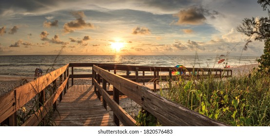 Boardwalk leading toward Delnor-Wiggins State Park at sunset in Naples, Florida.