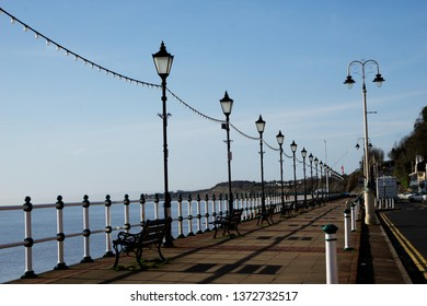 The boardwalk near the pier with a line of street lights near the ocean with the mountains in the background in Penarth, Wales, in England.