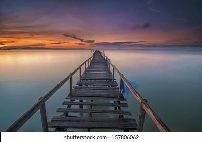Boardwalk on beach at sunrise . Teluk Tempoyak, Penang, Malaysia. Copy Space Area