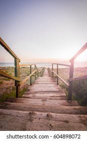 Boardwalk on a beach at sunset