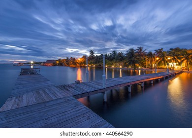 Boardwalk at Sunset in Placencia, Belize with trees and lights in the background.