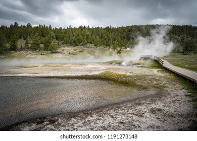 Boardwalk through a steamy thermal feature in Yellowstone National Park, along Firehole Drive, featuring many geological wonders and hot springs