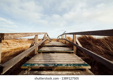 Boardwalk trail crossing seashore landscape with dry grass, viewed from the top of old wooden stairs on the hill. Idyllic picturesque landscape with cloudy sky, Amrum, Germany